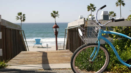 Blue bicycle, cruiser bike by ocean beach, pacific coast, Oceanside California USA. Summertime vacations sea shore. Vintage cycle by wooden stairs, stairway or staircase. Tropical palms and lifeguard Standard-Bild