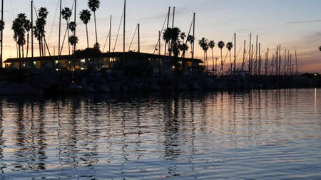Luxury yachts sailboats floating, marina harbour quay. Sail boat masts, nautical vessels in port. Harbor fisherman village in Oceanside, California USA. Evening dusk, twilight lights and palm trees.