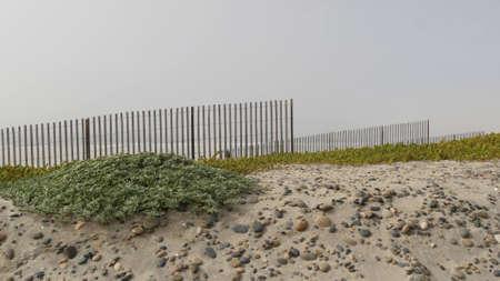 Wooden picket fence, sandy misty beach, Encinitas California USA. Pacific ocean coast, dense fog on empty sea shore. Coastline near Los Angeles, boards in milky smog haze. Gloomy weather on shoreline.