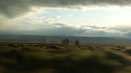 Driving auto, road trip in California, USA, view from car. Hitchhiking traveling in United States. Highway, mountains and cloudy dramatic sky before rain storm. American scenic byway. Passenger POV.