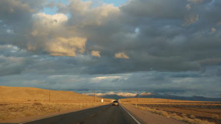 Road trip, driving auto from Death Valley to Las Vegas, Nevada USA. Hitchhiking traveling in America. Highway journey, dramatic atmosphere, sunset mountain and Mojave desert wilderness. View from car. Standard-Bild