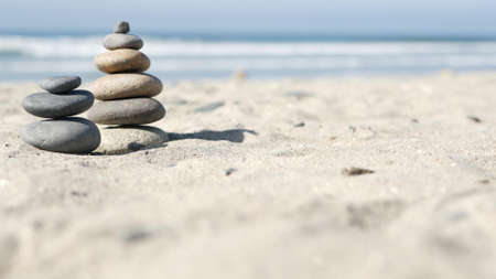 Rock balancing on ocean beach, stones stacking by sea water waves. Pyramid of pebbles on sandy shore. Stable pile or heap in soft focus with bokeh, close up. Zen balance, minimalism, harmony and peace Archivio Fotografico