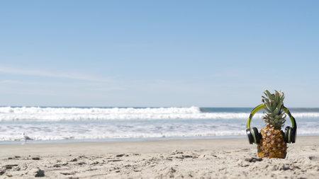 Funny pineapple in headphones, sandy ocean beach, blue sea water waves, California pacific coast, USA. Tropical summer exotic fruit enjoying vacations and music in paradise. Ananas sunbathing on shore Standard-Bild