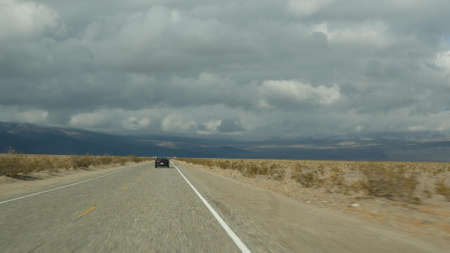 Road trip to Death Valley, driving auto in California, USA. Hitchhiking traveling in America. Highway, mountains and dry desert, arid climate wilderness. Passenger POV from car. Journey to Nevada. Standard-Bild