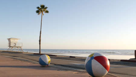 Pacific ocean beach, Oceanside California USA. Ball, lifeguard tower, life guard watchtower hut and tropical palm tree, sky, beachfront street, waterfront road. Los Angeles vibes, aesthetic atmosphere Standard-Bild