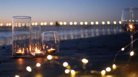 Candle flame lights in glass, romantic beach date, California ocean waves, sea water. Candlelight seamless looped cinemagraph. Wineglass on sand, garland in twilight dusk. Illuminated pier reflection. Standard-Bild