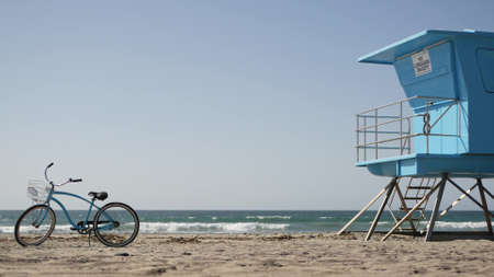 Blue bicycle, cruiser bike by ocean beach, pacific coast, Oceanside California USA. Summertime vacations, sea shore. Vintage cycle on sand near lifeguard tower or watchtower hut. Sky and water waves.