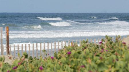 Blue turquoise water surf, big tide waves on sunny summer beach, Encinitas shoreline, California USA. Pacific ocean coast, greenery and wooden picket fence on sea shore. Coastline near Los Angeles.