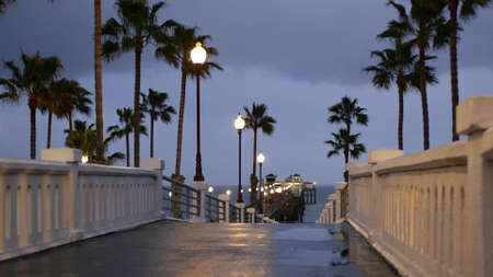 Rain drops, evening dark sky with clouds, Oceanside California USA. Empty pier and palm trees in twilight dusk. Reflection of lantern lights, illuminated wet broadwalk. Pacific ocean beach at night.