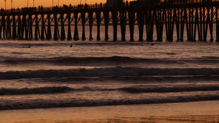 Wooden pier silhouette at sunset, California USA, Oceanside. Waterfront surfing resort, pacific ocean tropical beach. Summertime sea coastline vacations atmosphere. Surfers waiting for wave in water. Standard-Bild