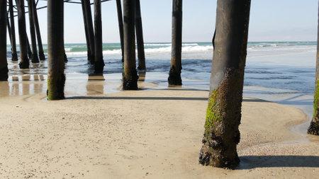 Wooden piles under boardwalk, old pier in Oceanside, California coast USA. Pilings, pylons or pillars below retro vintage bridge, waterfront promenade. Ocean waves, sea water tide and sand beach. Standard-Bild