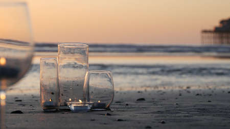 Candle flame lights in glass, romantic beach date by California ocean waves, summer sea water. Candlelight seamless looped cinemagraph. Wineglass, glass for wine on littoral sand. Cozy lounge, sunset. Banque d'images