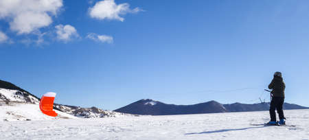 snowkiting: The snowkiting raises the sail to the wind on the snow-covered valley