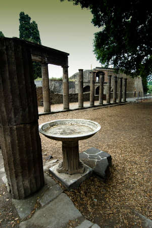social history: Columns of the triangular hole with holy water in Pompeii Pompeii is a ruined and partially buried Roman town-city near modern Naples in the Italian region of Campania, in the territory of the comune of Pompei. Stock Photo
