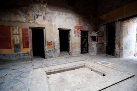 social history: The impluvium of large fountain House in Pompeii. Pompeii is a ruined and partially buried Roman town-city near modern Naples in the Italian region of Campania, in the territory of the comune of Pompei.