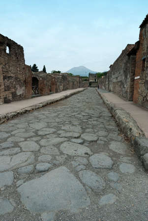 historic world event: Street in Pompeii Pompeii is a ruined and partially buried Roman town-city near modern Naples in the Italian region of Campania, in the territory of the comune of Pompei. Stock Photo