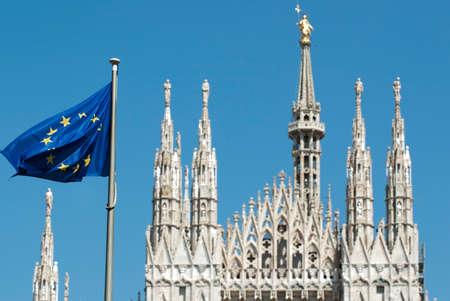Flaping bandera europea en Milán Plaza de la Catedral (Piazza del Duomo) desenfoque. La catedral de Milán (en italiano: Duomo di Milano) es la Iglesia Catedral de Milán en Lombardía, norte de Italia. Foto de archivo - 38604223