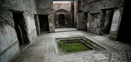 The impluvium of large fountain House in Pompeii. Pompeii is a ruined and partially buried Roman town-city near modern Naples in the Italian region of Campania, in the territory of the comune of Pompei.  Stock Photo