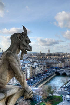 convey: Gargoyle looking at Paris. In architecture, a gargoyle is a carved stone grotesque with a spout designed to convey water from a roof and away from the side of a building. Stock Photo