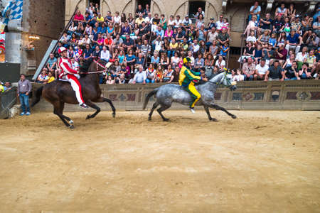 Siena, Italy - June 29, 2014: horses run on the straight under the stands of the spectators in Palio of Siena in tuscan, Italy. Medieval horse races the Palio of Siena in Tuscan Italy.