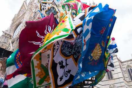 palio: Flags of the contrada of palio Siena, waving in front of the cathedral Editorial