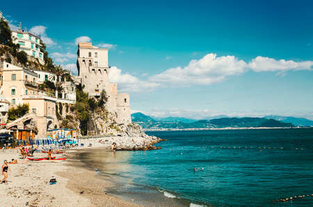 holidays vacancy: Cetara, Italy - October 2, 2013: Cetara small beach village on the Amalfi Coast, LA beach is defended by an ancient Saracen tower. Bathers on the beach on a warm October day. In the background you can see the city of Salerno Editorial