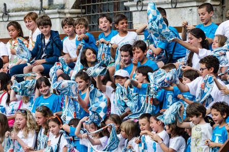 palio: Siena, Italy - July 29, 2014: Boys rejoice and sing a chorus of encouragement during the Palio of Siena. Tribune of the spectators in Palio of Siena in tuscany, Italy. Medieval horse races the Palio of Siena in Tuscan Ita