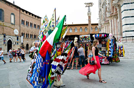 palio: Siena, Italy - June 29, 2014: selling flags to the Palio of Siena, in a kiosk in the square of the cathedral Italy. Medieval horse races the Palio of Siena in Tuscan Italy.