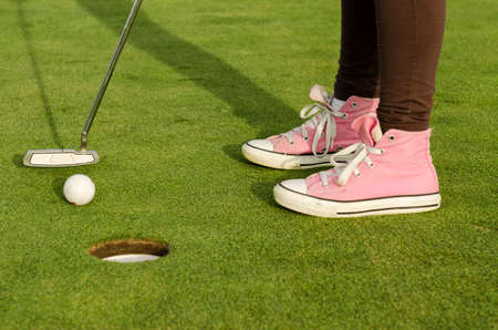 men s feet: girl plays golf with pink sneakers.