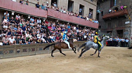 Siena Italy  June 29 2014: horses run on the straight under the stands of the spectators in Palio of Siena in tuscan Italy. Medieval horse races the Palio of Siena in Tuscan Italy. Sajtókép