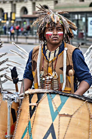 sioux: Turin Italy  April 27 2013: Red indian in traditional costume plays in the center of Turin Italy. Street performance of a group of Native Americans with sounds and traditional dancing.