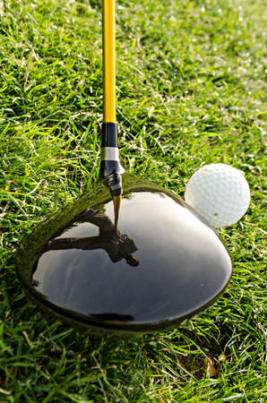 golf ball on tee: golf ball tee and grass with reflection of the player