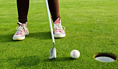 teen golf: ni�a juega al golf con zapatillas de color rosa.