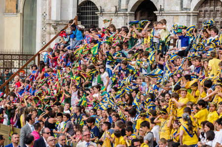 palio: Siena Italy  July 29 2014: Boys rejoice and sing a chorus of encouragement during the Palio of Siena. Tribune of the spectators in Palio of Siena in tuscany Italy. Medieval horse races the Palio of Siena in Tuscan Ita Editorial