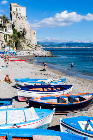 bathers: Cetara Italy  October 2 2013: Cetara small beach village on the Amalfi Coast LA beach is defended by an ancient Saracen tower. Bathers on the beach on a warm October day. In the background you can see the city of Salerno