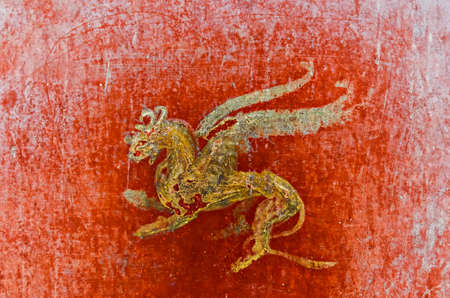 italian fresco: detail of the fresco in Pompeii with winged griffin on a red background PompeianPompeii is a ruined and partially buried Roman towncity near modern Naples in the Italian region of Campania in the territory of the comune of Pompei. Along with Herculaneum i
