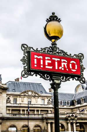 traditional Paris red metro sign against the backdrop of the building Editorial