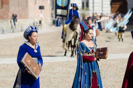 edad media: Asti, Italia - 16 septiembre 2012: Procesión de artistas callejeros en trajes medievales desfilando en el Palio de Asti. Un par de manera noble en la Edad Media