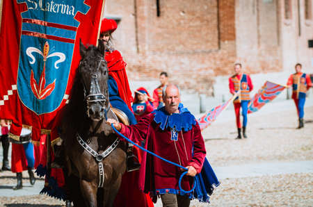 palio: Asti, Italy - September 16, 2012: Procession of street performers in medieval costumes parading in the Palio of Asti. Medieval knight on horseback