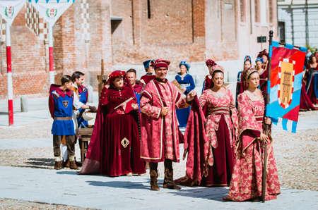 Asti, Italië - 16 september 2012: Optocht van straatartiesten in middeleeuwse kostuums paraderen in de Palio van Asti. Een groep van nobele de mode in de Middeleeuwen Stockfoto - 51490622
