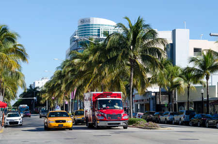 traffic: Miami, Florida - February 15, 2015: Taxi drives fermo al semaforo on South Beachs Ocean Drive in Miami. Collins Avenue in Miami Beach is home to many of world famous and historic Art Deco hotels in South Beach