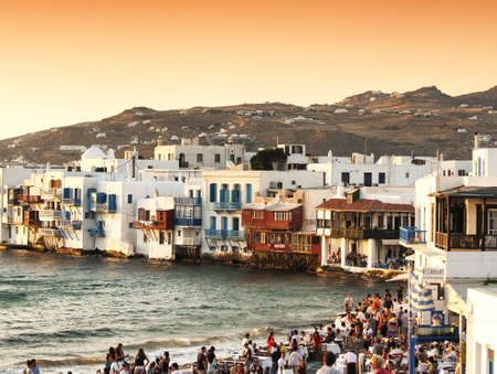 myconos: Mykonos, Greece - June 17, 2009: Tourists sitting at a bar on the beach while watching the sun set into the sea in the beautiful Mykonos island Cyclades Greece