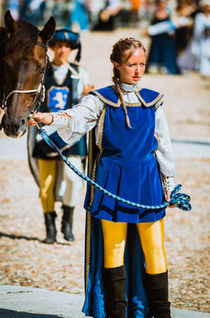 procession: Asti, Italy - September 16, 2012: Procession of street performers in medieval costumes parading in the Palio of Asti. Squire female holds his horse by the bridle Editorial