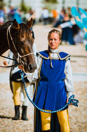 squire: Asti, Italy - September 16, 2012: Procession of street performers in medieval costumes parading in the Palio of Asti. Squire female holds his horse by the bridle Editorial