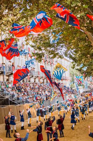 vestidos de epoca: Asti, Italia - 16 septiembre 2012: el desfile medieval hist�rica del Palio de Asti, en el Piamonte, Italia. Acr�batas de banderas realizan en la pista de carreras de caballos, desfile de banderas ondeando en Palio medieval
