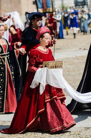 vestidos de epoca: Asti, Italia - 16 septiembre 2012: desfile de damas de honor con la catedral al fondo en trajes medievales desfilando en el Palio de Asti. Desfile de la dama de honor con el ataúd de metales preciosos