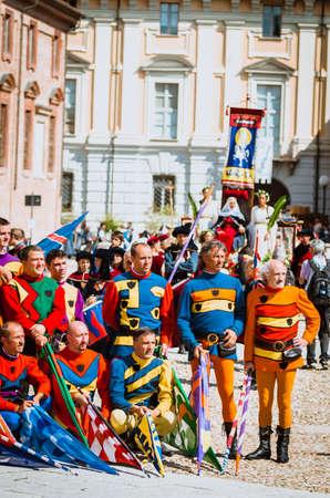 edad media: Asti, Italia - 16 septiembre 2012: Procesi�n de artistas callejeros en trajes medievales desfilando en el Palio de Asti. Pareja de manera noble en la Edad Media. portadores de la bandera desfile de la Edad Media en frente de la catedral de la ciudad de Asti.