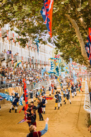 palio: Asti, Italy - September 16, 2012: the historical Medieval parade of the Palio of Asti in Piedmont, Italy. Acrobats of flags perform on the race track of horses, flag-waving parade in medieval Palio Editorial