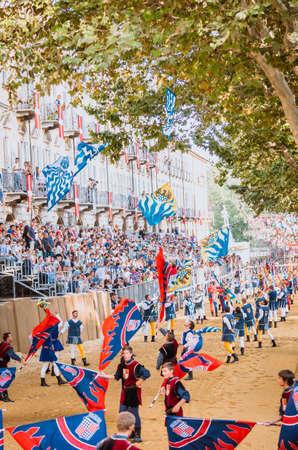 vestidos de epoca: Asti, Italia - 16 septiembre 2012: el desfile medieval histórica del Palio de Asti, en el Piamonte, Italia. Acróbatas de banderas realizan en la pista de carreras de caballos, desfile de banderas ondeando en Palio medieval