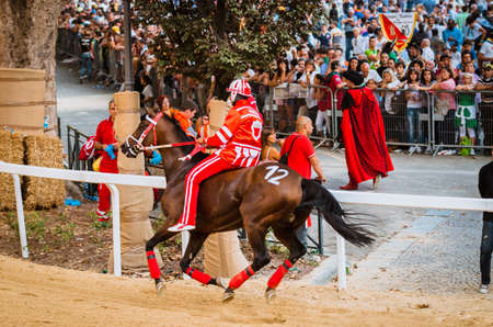 palio: Asti, Italy - September 15, 2012: horses run on the straight under the stands of the spectators in Palio of Asti in Piedmont, Italy. Medieval horse races the Palio in Asti, Italy. Editorial